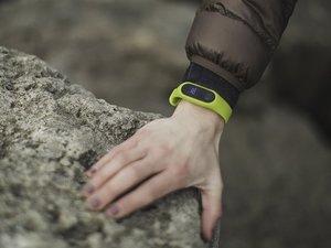 green fitbit on wrist