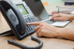 Employee using VoIP phone and computer simultaneously