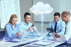 A group of people using cloud computing at a conference room table.